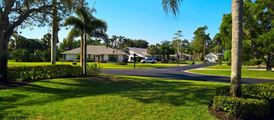 View of the golf resort with family houses, lawn and palm trees along the road under blue sky in Naples, Florida, USA